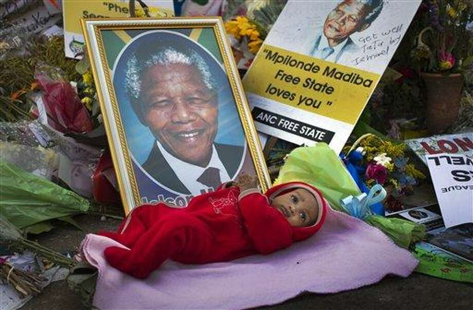 Oamohetswe Mabitsela, 4 months old, is placed by his mother next to a picture of Nelson Mandela for her to take a photograph of him with her camera phone, outside the Mediclinic Heart Hospital where former South African President Nelson Mandela is being treated in Pretoria, South Africa Thursday, July 4, 2013. The remains of Nelson Mandela's three deceased children were reburied at their original resting site on Thursday, a day after a court ordered their return two years after Mandela's grandson moved the bodies. (AP Photo/Ben Curtis) Photo: AP / AP