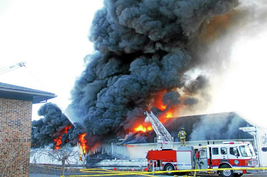 ESTEBAN L. HERNANDEZ — THE REGISTER CITIZEN Firefighters from Torrington and dozens of other departments battled a five-alarm blaze at Toce Brothers Inc., a warehouse full of tires, on Albert Street in Torrington on April 3. Photo: Journal Register Co.
