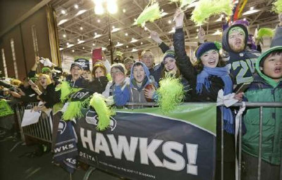 Fans greet Seattle Seahawks players and coaches during the team's arrival at Seattle-Tacoma International Airport, Monday, Feb. 3, 2014, in Seattle.