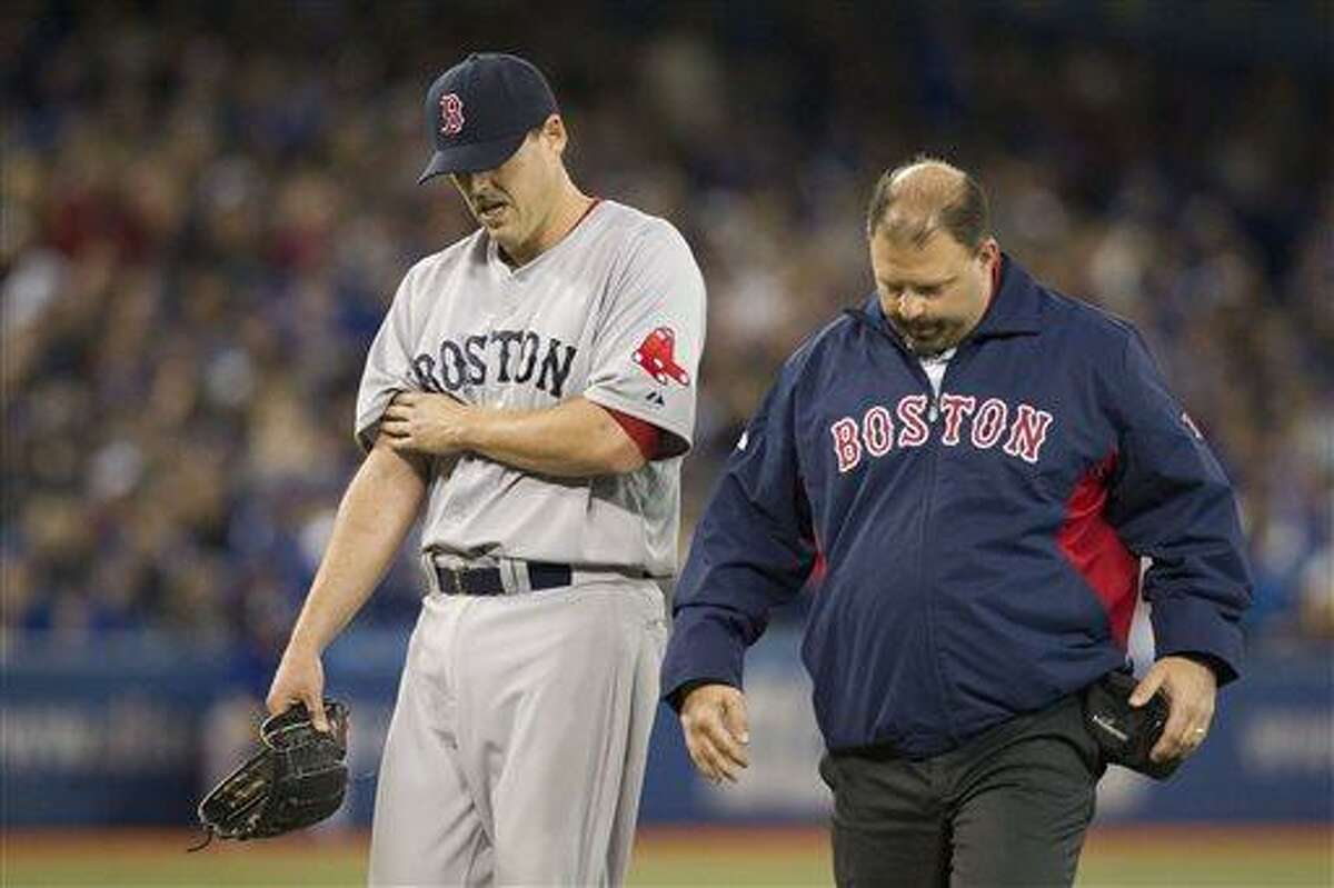 Boston Red Sox pitcher John Lackey, left, walks off the field with trainer Rick Jameyson after he was relieved in the fifth inning of a baseball game against the Toronto Blue Jays in Toronto on Saturday, April 6, 2013.(AP Photo/The Canadian Press)