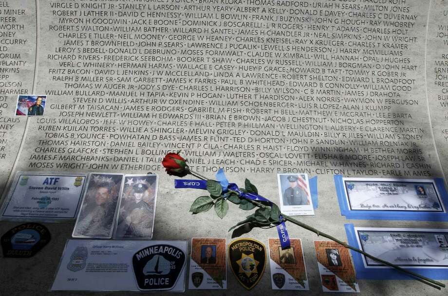 In this May 13, 2013 photo, a rose is placed at the wall with the names of fallen police officers at the National Law Enforcement Officers Memorial in Washington during the National Police Week. Photo: AP Photo/Jose Luis Magana, File  / FR159526 AP