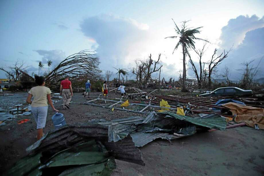 """Residents walk by debris after powerful Typhoon Haiyan slammed into Tacloban city, Leyte province, central Philippines on Saturday, Nov. 9, 2013. The central Philippine city of Tacloban was in ruins Saturday, a day after being ravaged by one of the strongest typhoons on record, as horrified residents spoke of storm surges as high as trees and authorities said they were expecting a """"very high number of fatalities."""" (AP Photo/Aaron Favila) Photo: AP / AP"""