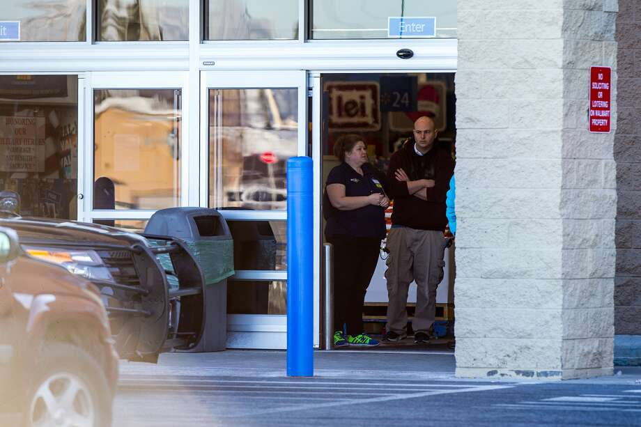 People stand inside a Walmart in Hayden, Idaho, Tuesday, Dec. 30, 2014. A 2-year-old boy accidentally shot and killed his mother after he reached into her purse at the northern Idaho Wal-Mart and her concealed gun fired, authorities said Tuesday. Photo: (AP Photo/Coeur D'Alene Press, Tess Freeman) / Coeur d'Alene Press