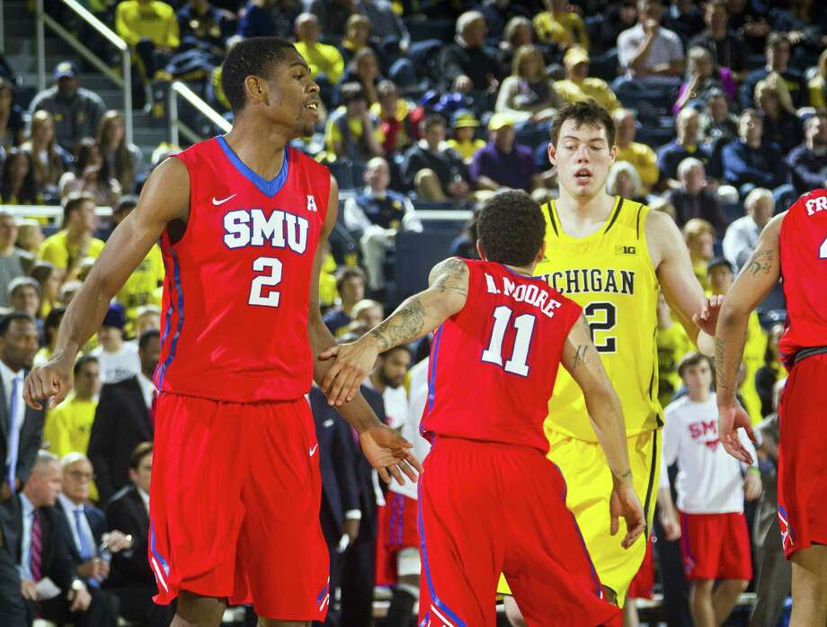 SMU center Yanick Moreira (2) and guard Nic Moore (11) celebrate after a basket during a recent game. Photo: The Associated Press File Photo  / FR143848 AP