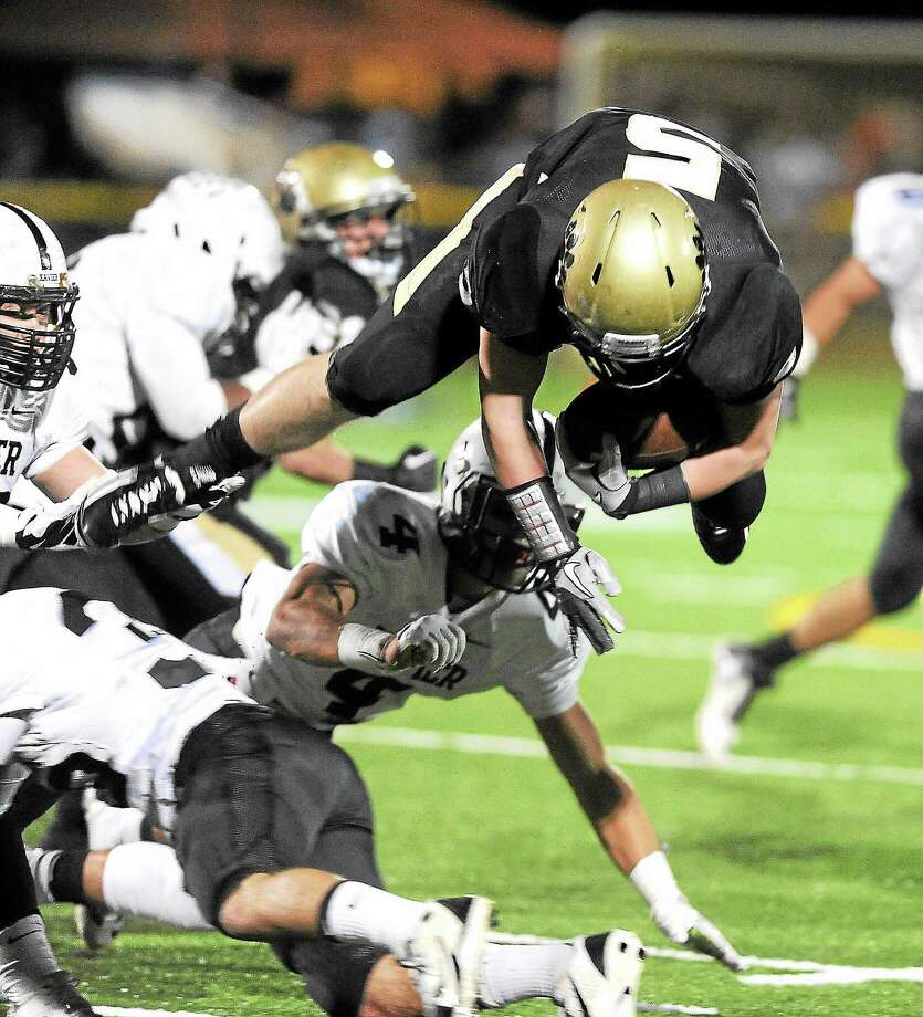 (Peter Casolino — New Haven Register)  Hand's Conor Dowd gets upended in the second quarter by the Xavier defense, including Nathan Gozalez (#4).  pcasolino@NewHavenRegister Photo: Journal Register Co.