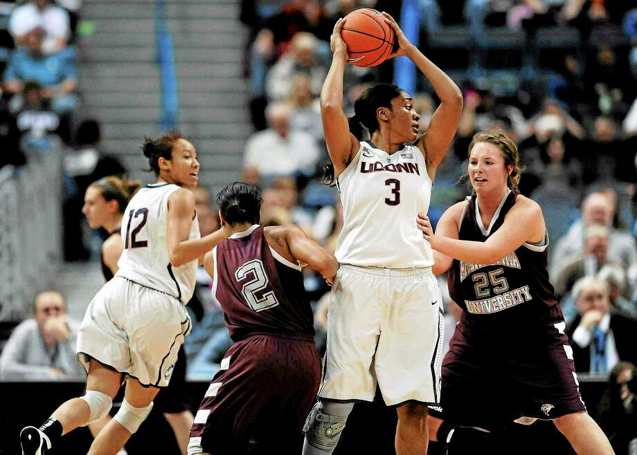 UConn's Morgan Tuck (3), looks to pass while being pressured by Philadelphia's Bria Young (2) and Jackie McCarron (25) as the Huskies' Saniya Chong (12) cuts to the basket during the second half of an exhibition game Tuesday in Hartford. Photo: Jessica Hill — The Associated Press  / FR125654 AP