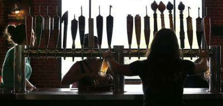 In this July 1, 2013 photo, a bartender pours two drafts from a selection of about 20 beverages on tap at the Beer Hall at the Harpoon Brewery in the Seaport District of Boston. The neighborhood around the brewery is transforming from a waterfront industrial area to one that hosts upscale restaurants, luxury hotels and an art museum. (AP Photo/Charles Krupa) Photo: AP / AP