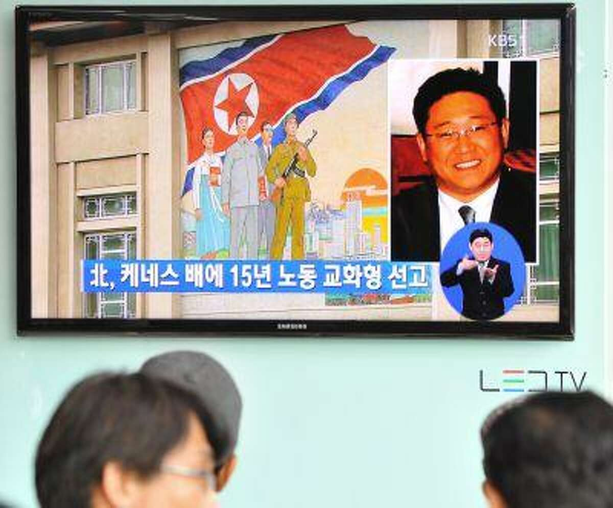 Passersby watch a local television broadcast in Seoul on May 2, 2013, showing a report and picture of Kenneth Bae, a Korean-American tour operator detained in North Korea, against the background of a North Korean flag painted on the wall of a building in Pyongyang.