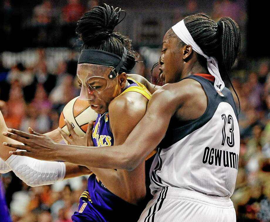 The Los Angeles Sparks' Nneka Ogwumike, left, is guarded by her sister Chiney, right, of the Connecticut Sun during the first half Sunday in Uncasville. Photo: Jessica Hill — The Associated Press  / FR125654 AP