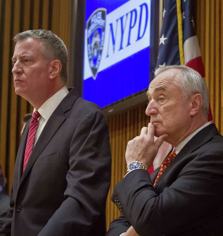 Mayor Bill de Blasio, left, and NYPD Commissioner Bill Bratton, right, listen during a press conference after attending a promotion ceremony for police officers on Dec. 19, 2014 in New York. Photo: AP Photo/Bebeto Matthews  / AP