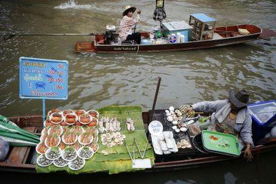 It holds a UNESCO World Heritage Award for its main canal. Vendors offer food from their small boats to people visiting the market at Samut Songkhram province March 16. Photo: REUTERS / X90027