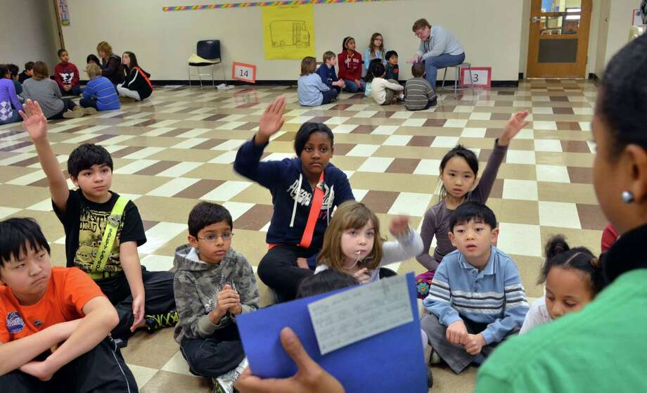 Students raise their hands as an elementary school teacher questions what is and isn't appropriate behavior aboard a school bus in this file photo. Photo: File Photo