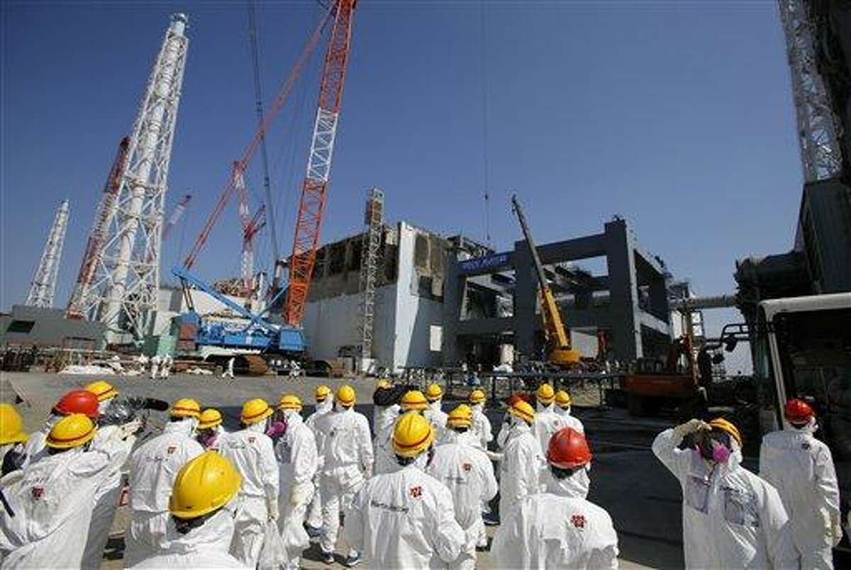 AP FILE - In this March 6, 2013 file photo, journalists wearing protective gears are escorted to the damaged No. 4 reactor building and an under construction foundation, center right, which will store the reactor's melted fuel rods, at Tokyo Electric Power Co.'s crippled Fukushima Dai-ichi nuclear power plant in Okuma town, Fukushima prefecture, northeast of Tokyo. The cooling system failed for a storage pool for fuel at one of the reactors at the tsunami-damaged nuclear plant in northeastern Japan Friday, April 5, 2013, - the second in a month, although there was no immediate danger from the breakdown. (AP Photo/Issei Kato, File)