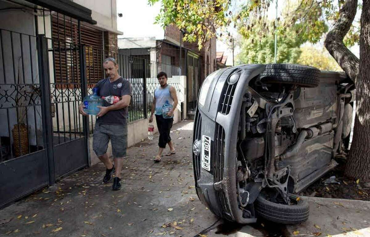 Men carry water past a car that flipped on its side during flooding in La Plata, in Argentina's Buenos Aires province, Thursday, April 4, 2013. Buenos Aires Gov. Daniel Scioli says 49 people died in this flooded capital of Argentinaís largest province as torrential rains swamped entire neighborhoods, washing away cars and flooding some houses to their rooftops. The overall death toll is now 55, and more than 20 people are missing. (AP Photo/Natacha Pisarenko)
