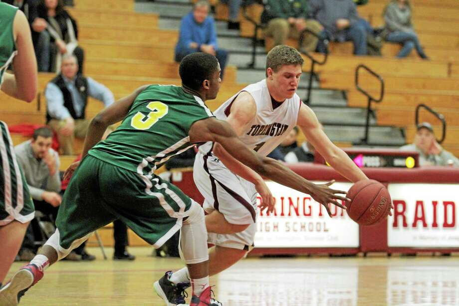 Torrington's Zak Mancini drives past Holy Cross's Jonathan Mowatt. Mancini finished with nine points in the Red Raiders come-from-behind, 72-70 win at home against the Crusaders. Senior John McCarthy scored on a lay up with seven seconds to lift Torrington. Photo: Marianne Killackey Special To The Register Citizen  / 2013