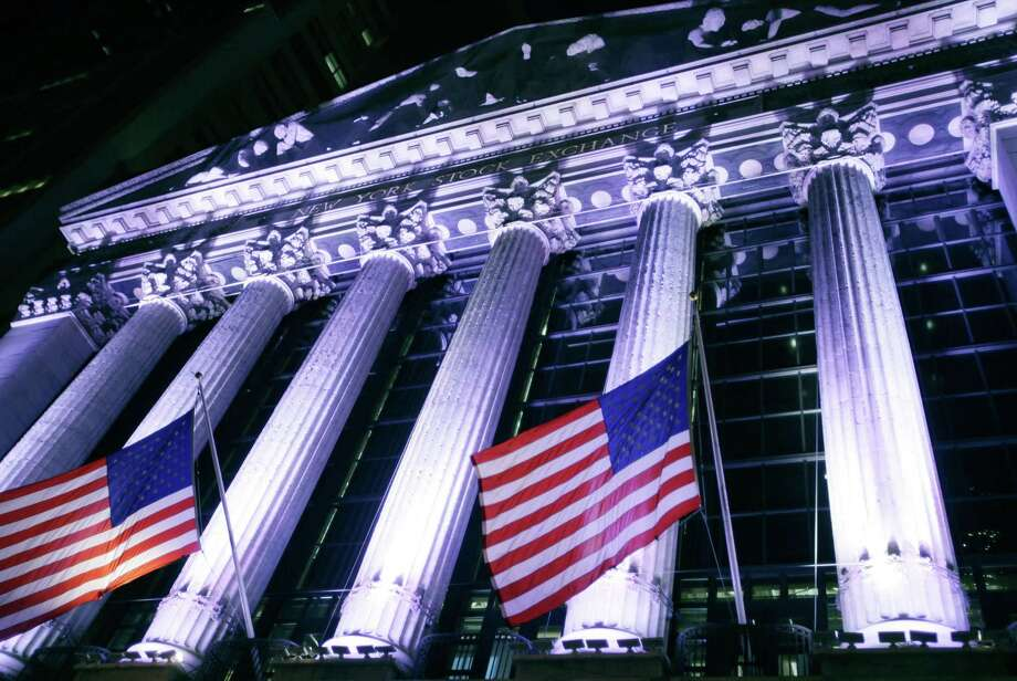In this Wednesday, Oct. 8, 2014 photo, American flags fly in front of the New York Stock Exchange. U.S. stocks were barely higher in early trading Monday, Dec. 29, 2014, as Wall Street winds down the year in this holiday-shortened week. Photo: THE ASSOCIATED PRESS / AP