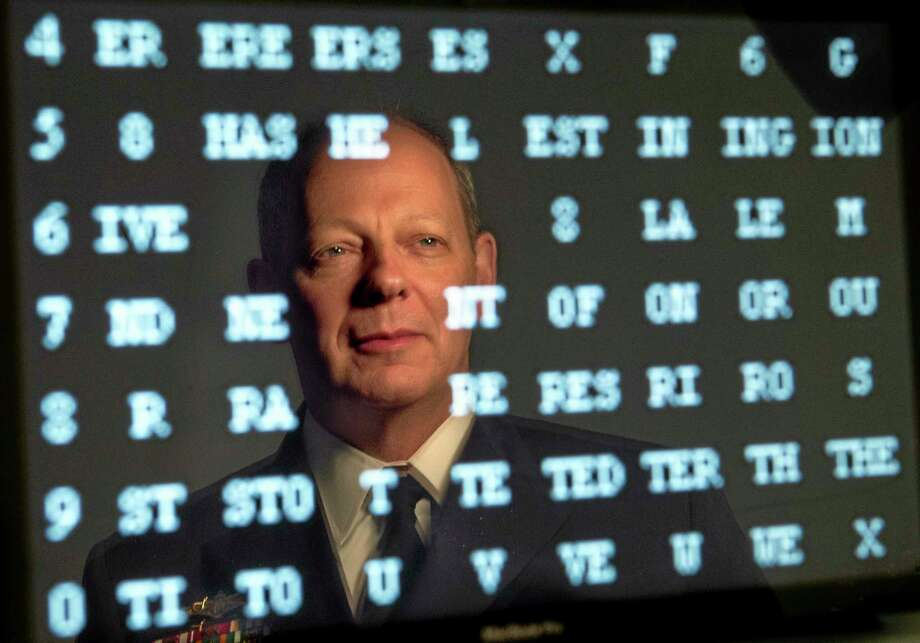 """Navy Rear Admiral William E. Leigher, one of the nation's top military experts on cyber security, is reflected in a computer screen displaying a numerical code, while posing Thursday, Nov. 7, 2013, in Portland, Maine. Leigher, who serves in the Pentagon as Director of Warfare Integration for Information Dominance, is an alumnus of the University of Southern Maine. He will keynote USM's second annual """"State of IT in Maine"""" conference, Friday, November 8. (AP Photo/Robert F. Bukaty) Photo: AP / AP"""