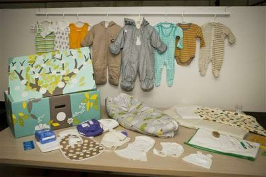 This photo taken on Aug. 15, 2012 shows the contents of the Finnish baby box, in Helsinki, Finland. Finland's social security service has given a baby box to Prince William and former Catherine Middleton, who are expecting their first baby in mid-July. The brightly colored cardboard box doubles as a cot, complete with mattress and sheets, and contains numerous baby items including a sleeping bag, jump suits, socks, pants, hats, bonnets and diapers. Maternity packages have been given to expectant mothers in Finland since 1938. (AP Photo/Lehtikuva, Roni Rekomaa) FINLAND OUT Photo: AP / Lehtikuva