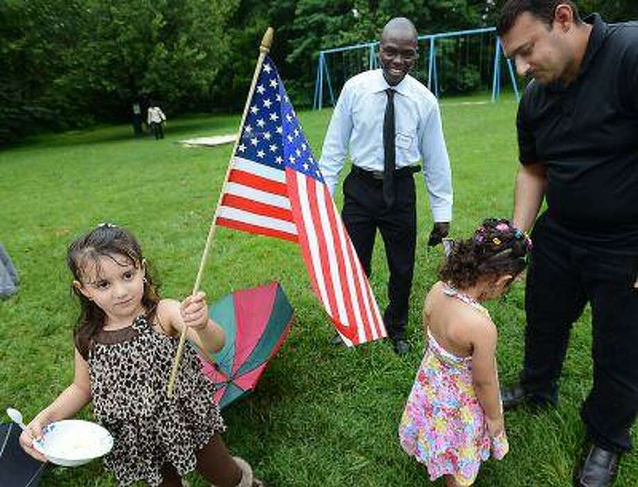 In this Tuesday, July 2, 2013 photo, Aisha Al Dulaimi, left, sister Noor Al Dulaimi with their father, Max, right, all from Iraq, and Adam Omar, center, from Sudan, celebrate Independence Day with American neighbors and new refugees in Durham, N.C. (AP Photo/The Herald-Sun, Bernard Thomas) Photo: AP / The Herald-Sun