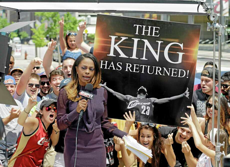 Fans whoop it up behind an ESPN reporter outside Quicken Loans Arena in Cleveland after LeBron James announced he would return to the Cavaliers on Friday. Photo: Mark Duncan — The Associated Press  / AP