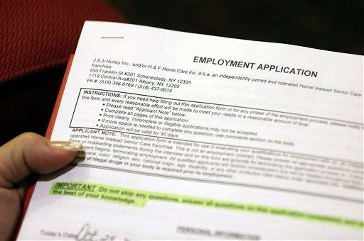 In this Thursday, Oct. 25, 2012, photo, Carmen Nazario of Albany, N.Y., fills out an employment application during a job fair at the Marriott Hotel in Colonie, N.Y. (AP Photo/Mike Groll)