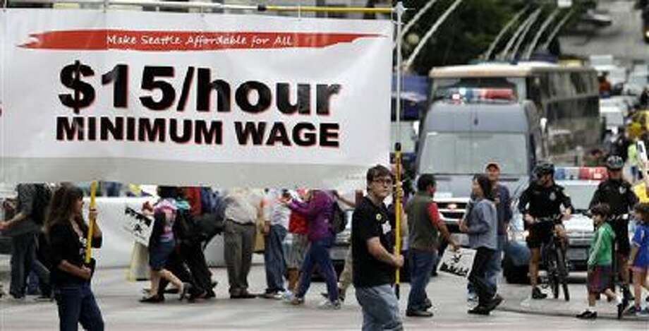 Demonstrators protesting what they say are low wages and improper treatment for fast-food workers march in downtown Seattle in August 2013. Photo: AP / AP