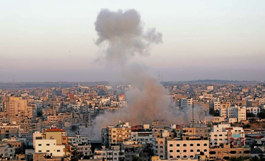 Smoke rises after an Israeli strike in Gaza City, Friday, July 11, 2014. Israel launched the Gaza offensive to stop incessant rocket fire that erupted after three Israeli teenagers were kidnapped and killed in the West Bank and a Palestinian teenager was abducted and burned to death in an apparent reprisal attack. The military says it has hit more than 1,100 targets already, mostly what it identified as rocket-launching sites, bombarding the territory on average every five minutes. (AP Photo/Hatem Moussa) Photo: AP / AP