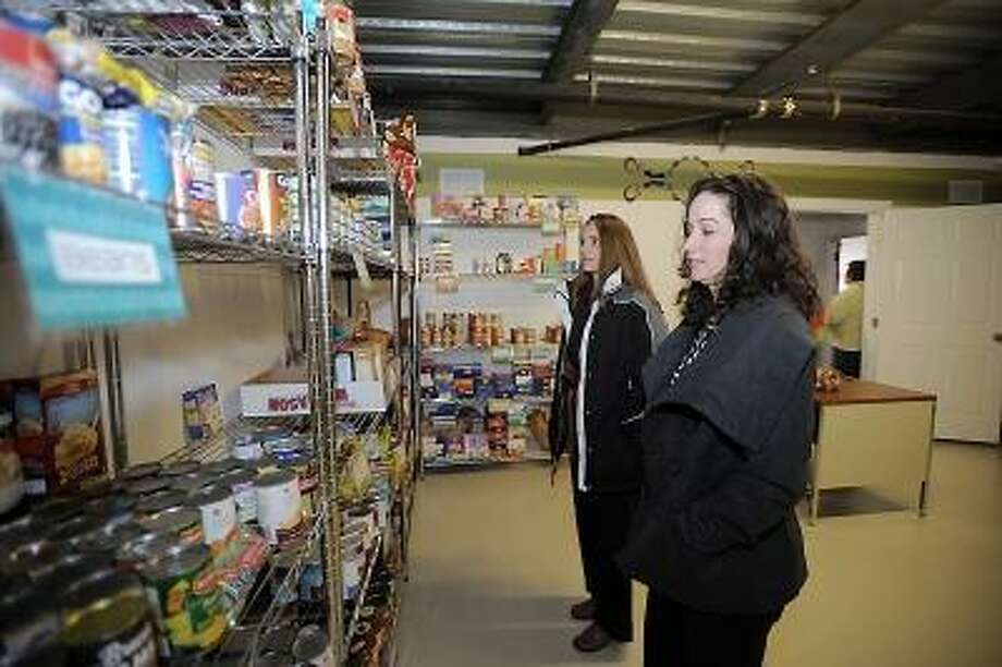 Laurie Gaboardi/Register Citizen Before the ribbon cutting on Friday, volunteers Breia Pinette and Brigitte Bousquet check out the shelves of the Harwinton Food Pantry.