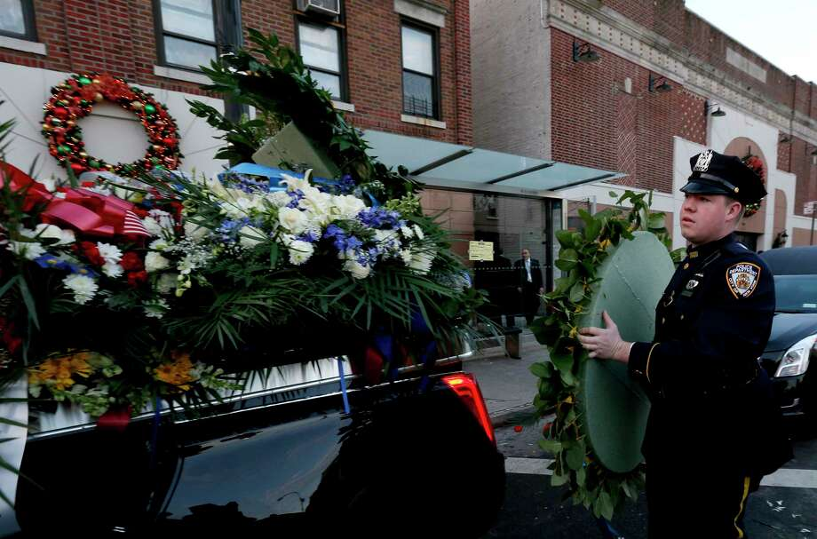 A New York Police Department officer loads flowers onto a vehicle outside of officer Rafael Ramos's funeral at Christ Tabernacle Church, in the Glendale section of Queens, Saturday, Dec. 27, 2014, in New York. Ramos and his partner, officer Wenjian Liu, were killed Dec. 20 as they sat in their patrol car on a Brooklyn street. The shooter, Ismaaiyl Brinsley, later killed himself. (AP Photo/Julio Cortez) Photo: AP / AP