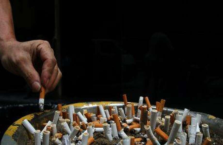 A man discards a cigarette butt outside a construction site. Photo: REUTERS / X01865