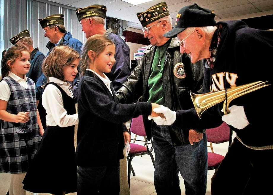 St. Mary-St. Michael School third grader Selena Hescock shakes hands with World War II Navy veteran Daniel R. Waleski after Veterans Day observances at the school Friday in Derby. Photo: Melanie Stengel — New Haven Register