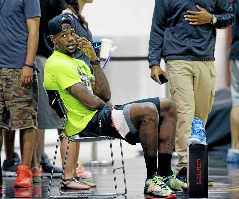 LeBron James speaks on a cellphone during the LeBron James Skills Academy Thursday in Las Vegas. Photo: John Locher — The Associated Press  / AP
