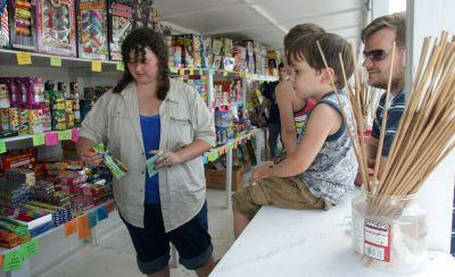 Pyro Dave's Fireworks stand worker Laura Siau ,left, gets sparklers for Mitch LaForest,right, of Silverdale while his sons Derek,3, center, and Blake,5, sit on the counter to get a close-up view on Friday June 28, 2013 in Bremerton, Wash. Friday was they first day the stand at 4220 Wheaton Way next to Shari's Restaurant in East Bremerton could sell fireworks. Fireworks are legal to sell in Kitsap County until July fourth. (AP Photo/Kitsap Sun, Larry Steagall) Photo: AP / KITSAP SUN