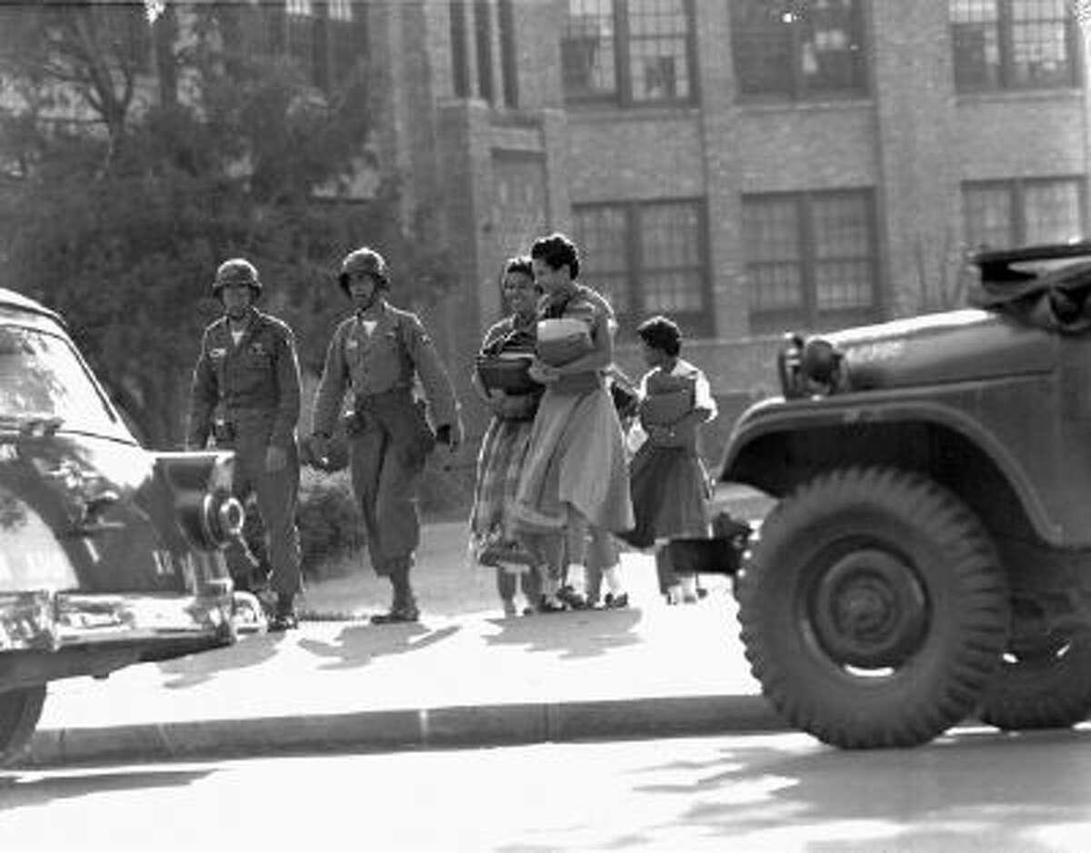 Two paratroop officers escort black students from Central High School in Little Rock, Ark., September 27, 1957. School was closing for the weekend.