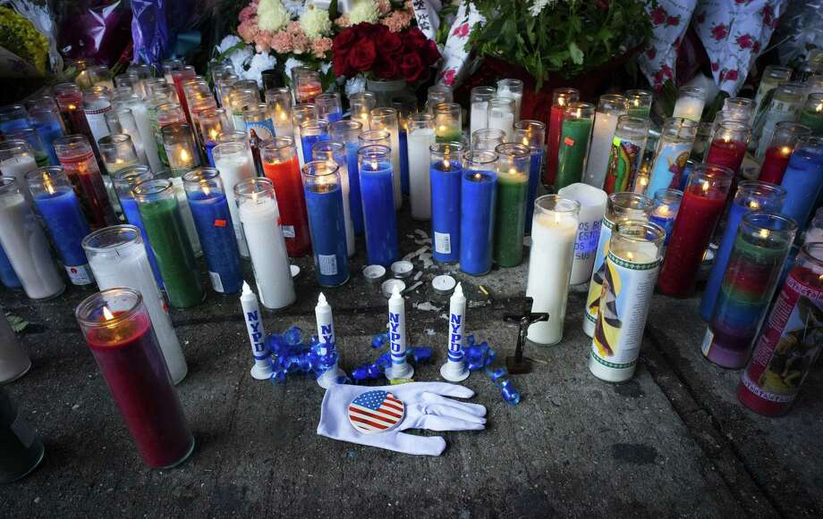 Candles and other items left by visitors make up a growing makeshift memorial Tuesday near the site where New York Police Department officers Rafael Ramos and Wenjian Liu were killed in the Brooklyn borough of New York. Photo: Associated Press  / FR61802 AP