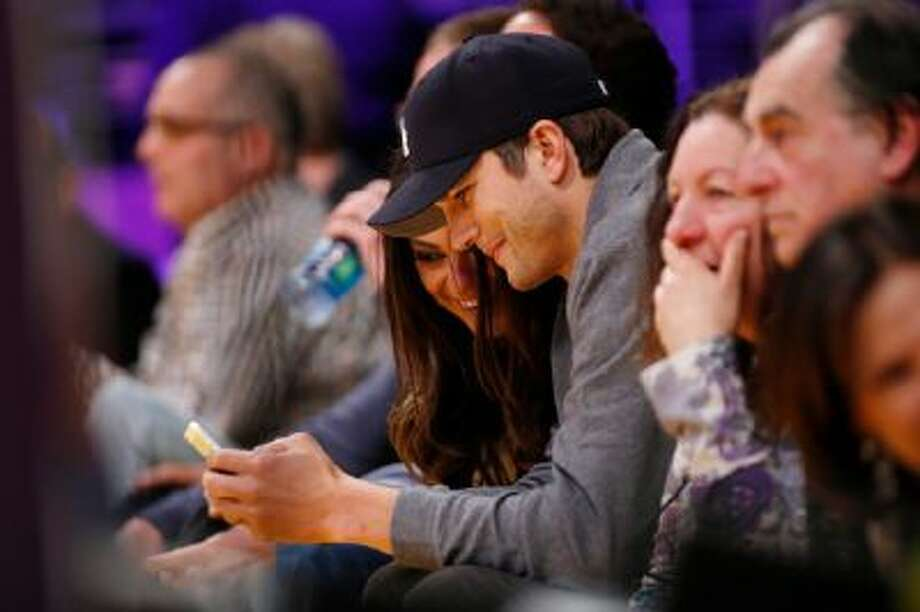 In this Feb. 12, 2013 photo, actors Mila Kunis, left, and Ashton Kutcher, right, look at a mobile phone as they sit courtside together at the NBA basketball game between the Phoenix Suns and Los Angeles Lakers, in Los Angeles.