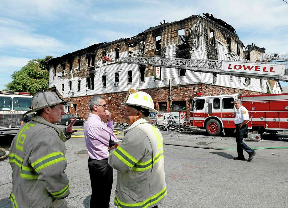 Fire officials observe the scene of a burned three-story apartment and business building in Lowell, Mass., Thursday, July 10, 2014, where officials said seven people died in a fast-moving pre-dawn fire. All seven victims were found in third-floor units of the three-story building that had businesses on the ground floor and apartments on the upper floors, fire officials said.  (AP Photo/Elise Amendola) Photo: AP / AP