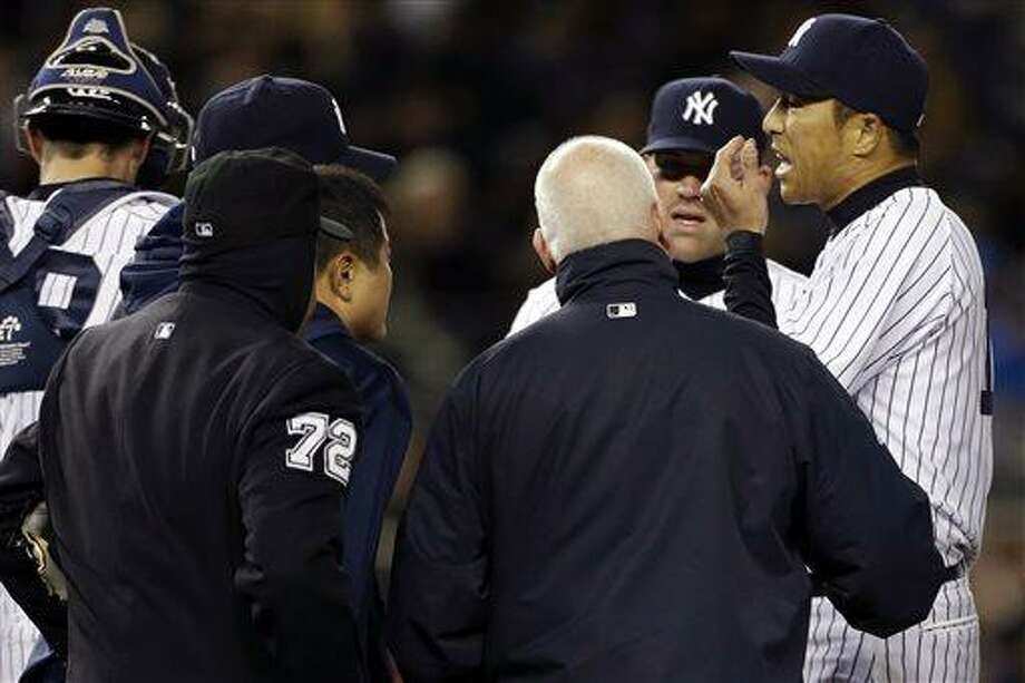 New York Yankees starting pitcher Hiroki Kuroda, far right, talks with head athletic trainer Steve Donohue and others after sustaining an injury in the second inning of a baseball game against the Boston Red Sox at Yankee Stadium in New York, Wednesday, April 3, 2013. (AP Photo/Kathy Willens) Photo: ASSOCIATED PRESS / AP2013