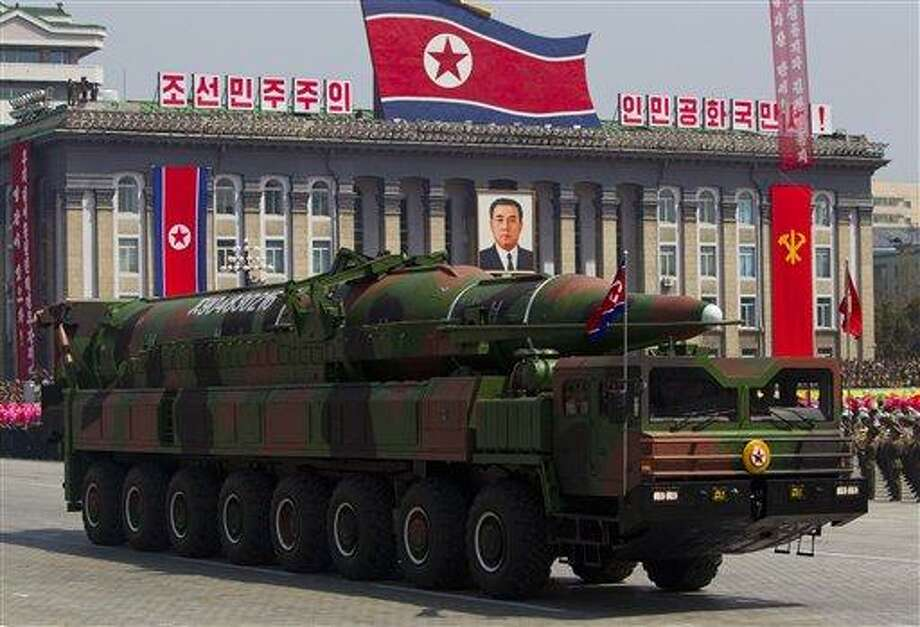 """FILE - In this Sunday, April 15, 2012 file photo, a North Korean vehicle carrying a missile passes by during a mass military parade in Pyongyang's Kim Il Sung Square to celebrate the centenary of the birth of the late North Korean founder Kim Il Sung. North Korea has moved a missile with """"considerable range"""" to its east coast, South Korean Defense Minister Kim Kwan-jin said Thursday, April 4, 2013 but he added that there are no signs that Pyongyang is preparing for a full-scale conflict. The report came hours after North Korea's military warned that it has been authorized to attack the U.S. using """"smaller, lighter and diversified"""" nuclear weapons. It was the North's latest war cry against America in recent weeks, with the added suggestion that it had improved its nuclear technology. (AP Photo/David Guttenfelder, File) Photo: AP / AP"""