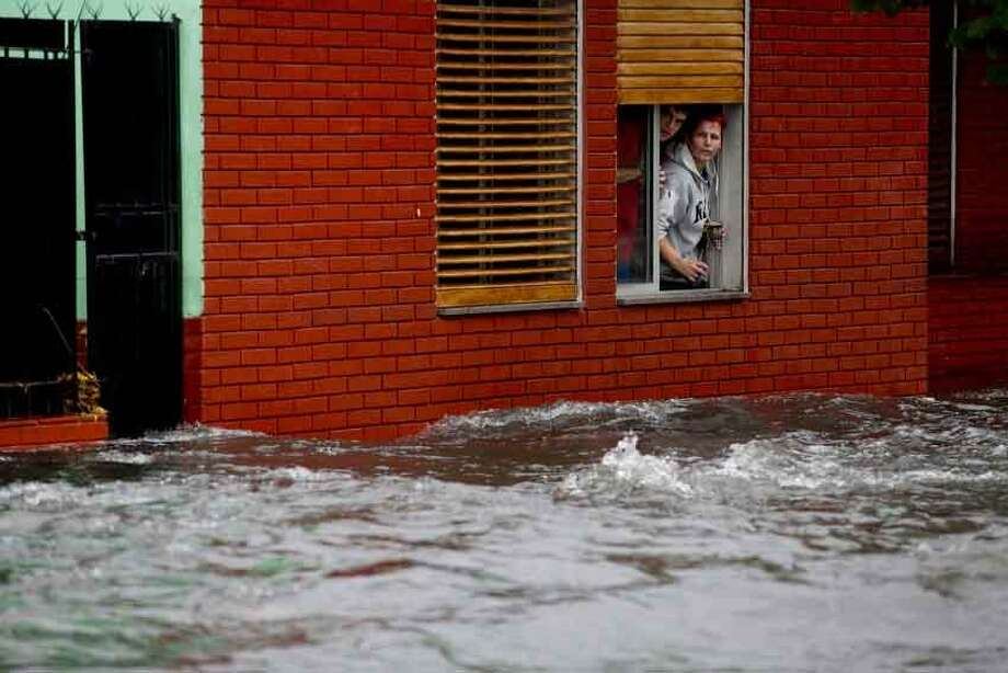 A couple looks at their flooded street from behind their home's window in La Plata, in Argentina's Buenos Aires province, Wednesday, April 3, 2013. At least 35 people were killed by flooding overnight in Argentina's Buenos Aires province, the governor said Wednesday, bringing the overall death toll from days of torrential rains to at least 41 and leaving large stretches of the provincial capital under water. (AP Photo/Natacha Pisarenko) Photo: ASSOCIATED PRESS / AP2013