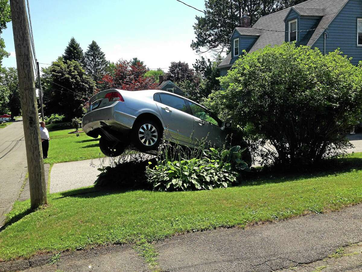 Robert McNulty's vehicle was stuck in the air after he accidentally accelerated through his garage and then reversed back over a boulder in front of his home at 123 Griswold St. in Torrington Thursday.