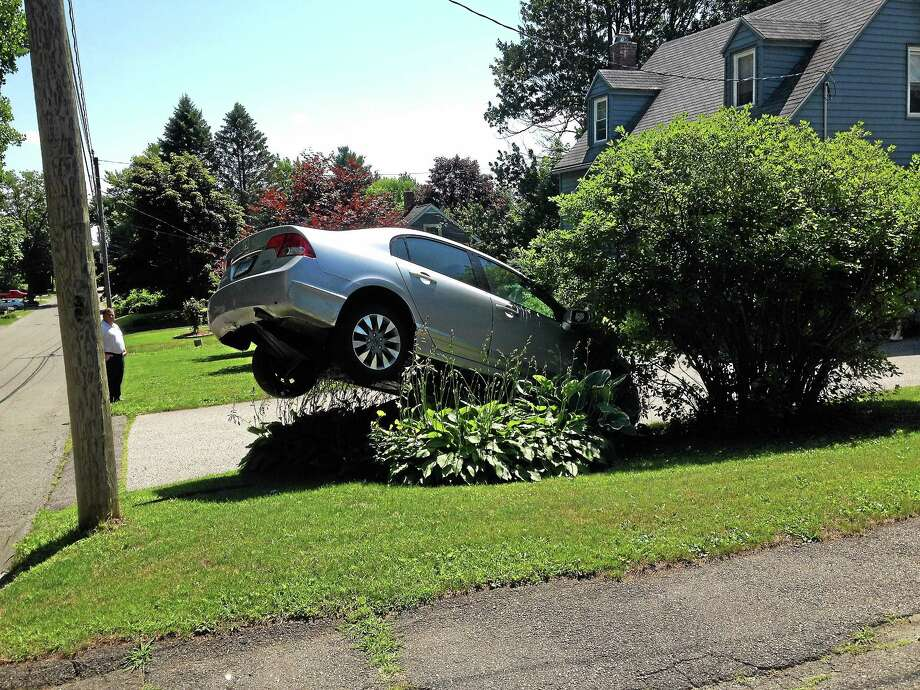 Robert McNulty's vehicle was stuck in the air after he accidentally accelerated through his garage and then reversed back over a boulder in front of his home at 123 Griswold St. in Torrington Thursday. Photo: Jenny Golfin — The Register Citizen