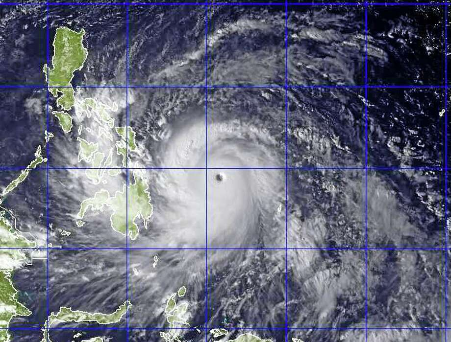 This image provided by the U.S. Naval Research Lab shows Typhoon Haiyan taken by the NEXSAT satellite Thursday Nov. 7, 2013 at 2:30 a.m. EDT. Gorvernment forecasters said Thursday that Typhoon Haiyan was packing sustained winds of 215 kilometers (134 miles) per hour and ferocious gusts of 250 kph (155 mph) and could pick up strength over the Pacific Ocean before it slams into the eastern Philippine province of Eastern Samar on Friday. (AP Photo/US Naval Research Lab) Photo: AP / U.S. Naval Research Lab