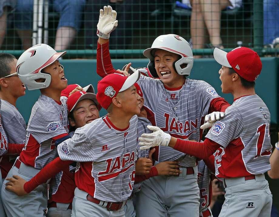 Japan's Seiya Arai (second from right) celebrates scoring the go-ahead run on a single by Natsuki Yajima in the fifth inning of the Little League World Series Championship game. Photo: Gene J. Puskar, Associated Press