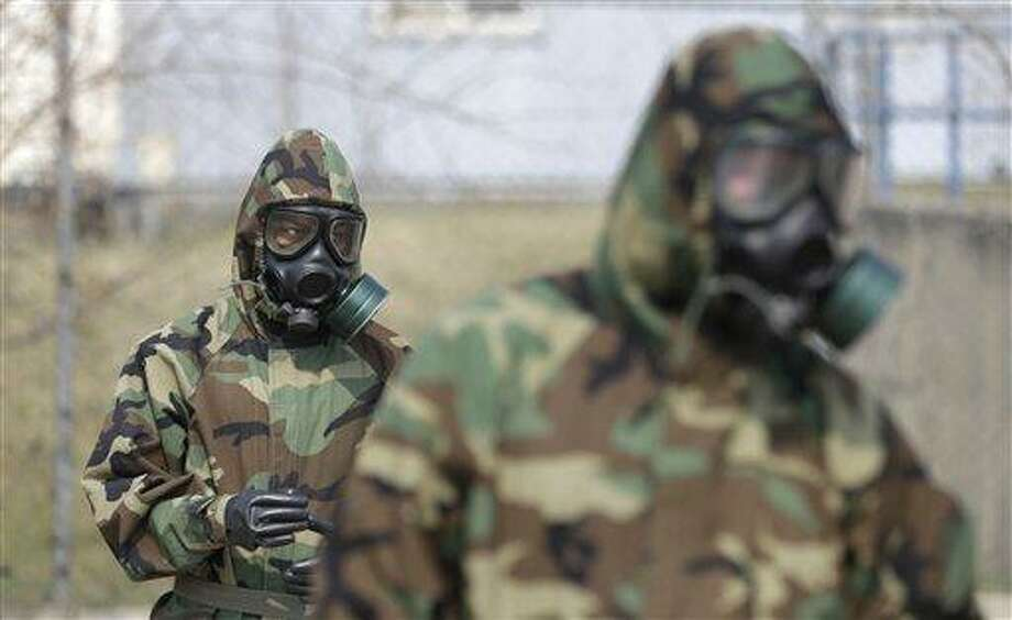 """Soldiers of the U.S. Army 23rd chemical battalion wear gas masks while attending a demonstration of their equipment during a ceremony to recognize the battalion's official return to the 2nd Infantry Division based in South Korea at Camp Stanley in Uijeongbu, north of Seoul, Thursday, April 4, 2013. The 23rd chemical battalion left South Korea in 2004 and returned with some 350 soldiers in Jan. 2013. The battalion will provide nuclear, biological and chemical detection, equipment decontamination and consequence management assistance to support U.S. and South Korean military forces. North Korea warned Thursday that its military has been cleared to attack the U.S. using """"smaller, lighter and diversified"""" nuclear weapons, while the U.S. said it will strengthen regional protection by deploying a missile defense system to Guam. (AP Photo/Lee Jin-man) Photo: AP / AP"""