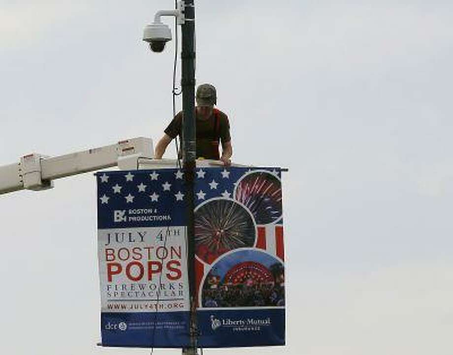 A worker installs a piece of security equipment on a lamp post on a bridge over the Charles River in Boston, Massachusetts July 2, 2013, in preparations for the city's Fourth of July celebrations. (Brian Snyder/Reuters) Photo: REUTERS / X90051