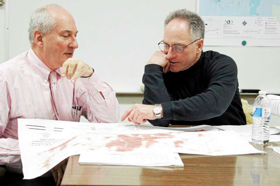 David Pavlick(left) and Curtis Barrows(right) are looking at a map in the Planning and Zoning Commission meeting. Photo: Shako Liu - The Register Citizen