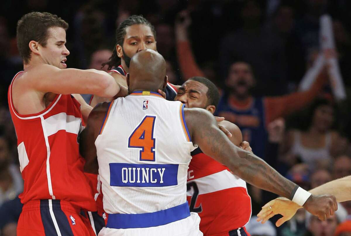Wizards forwards Kris Humphries, left, and Nene Hilario restrain Knicks forward Quincy Acy (4) and Wizards guard John Wall after Wall and Acy engaged in an on-court scuffle in the second half Thursday.