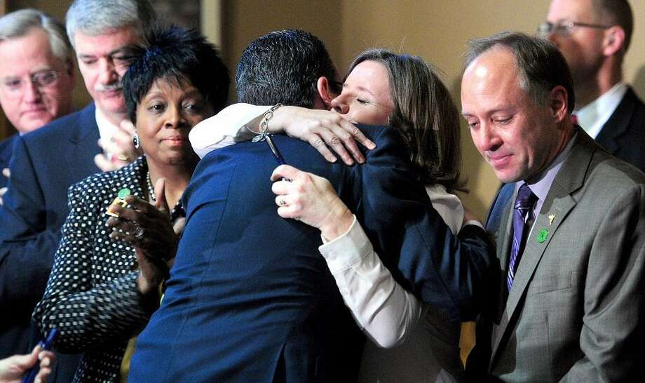 Governor Dannel Malloy (center-back to camera) hugs Jackie Barden after signing the Gun Violence Prevention and Child Safety Act at the Capitol in Hartford on 4/4/2013.  At right is Barden's husband, Mark.  The Bardens' son, Daniel, was  killed at Sandy Hook Elementary School.Photo by Arnold Gold/New Haven Register