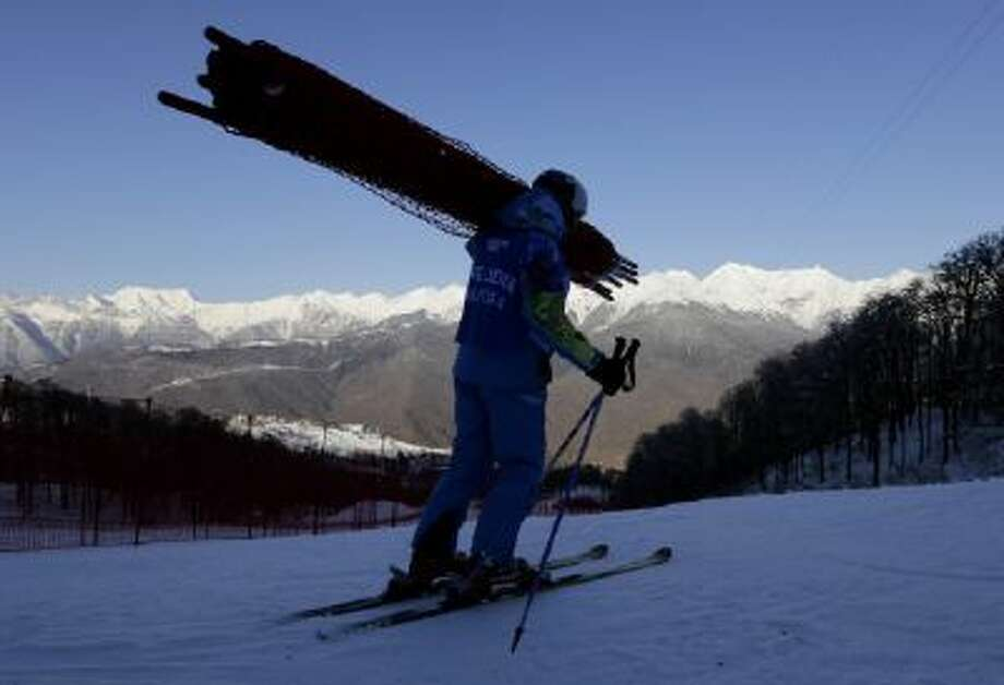 An Olympic worker carries safety fencing during final preparation of the Alpine ski course ahead of the Sochi 2014 Winter Olympics, Tuesday, Feb. 4, 2014, in Krasnaya Polyana, Russia.